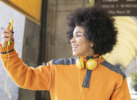 Smiling woman taking selfie through mobile phone standing outdoors - JCCMF01087