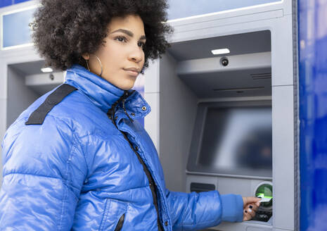 Afro woman removing ticket from ticket machine while standing bus stop - JCCMF01099