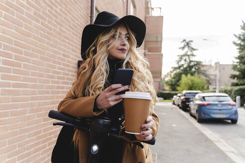 Young woman with electric push scooter holding reusable coffee cup while looking away - FMOF01325