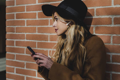 Young woman listening music through in-ear headphones against brick wall - FMOF01331