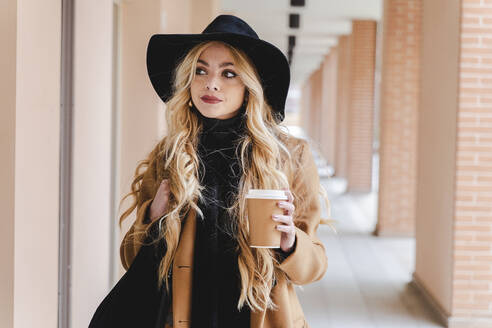 Woman with long hair holding coffee cup while looking away - FMOF01349
