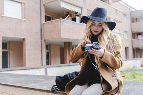 Blond woman sitting on retaining wall with vintage camera against building - FMOF01355