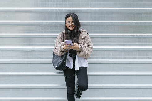 Smiling young woman using smart phone while moving down on staircase - JRVF00210