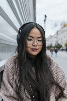 Beautiful woman with headphones against metal wall in city - JRVF00213