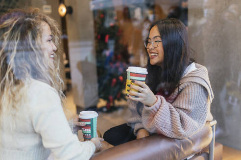 Young female friends having coffee while sitting in cafe seen through window glass - JRVF00219