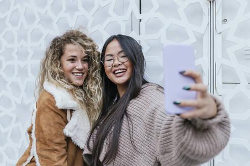 Beautiful female friends taking selfie through smart phone while standing against metal gate - JRVF00222