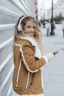 Smiling woman looking over shoulder while listening music over headphones - JRVF00243