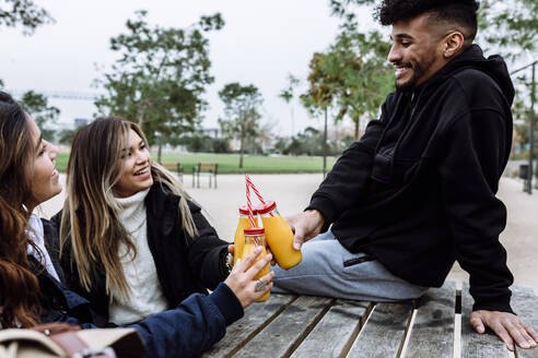 Happy friends toasting with orange juice bottle at park - XLGF01111