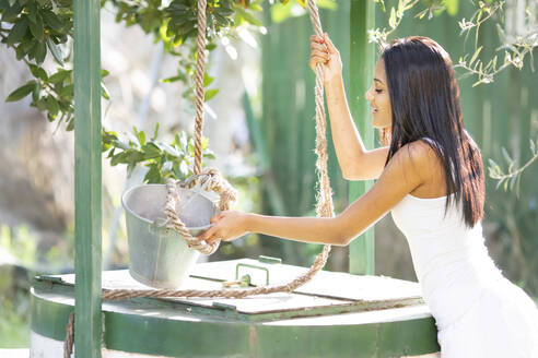 Woman pulling rope tied to bucket at water well while gardening in backyard - GGGF00946