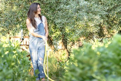 Smiling woman in bib overall watering plants through garden hose in backyard - GGGF00949