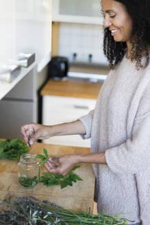 Smiling woman preparing herbal tea in kitchen - AKLF00028