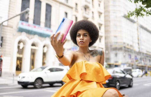 Afro woman taking selfie through mobile phone in city - JCCMF01146