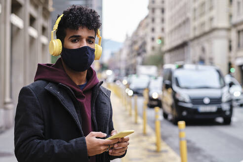 Man wearing jacket and protective face mask using mobile phone while standing on street in city - AGOF00003