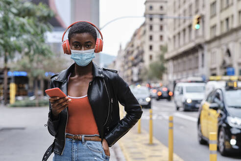 Woman wearing protective face mask and headphones using mobile phone while standing  - AGOF00006