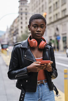 Woman wearing jacket and headphones using mobile phone while standing in city - AGOF00009