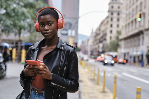 Woman wearing headphones and jacket using smart phone while standing in city - AGOF00012