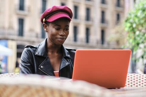 Smiling woman wearing cap working on laptop while sitting at sidewalk cafe - AGOF00021