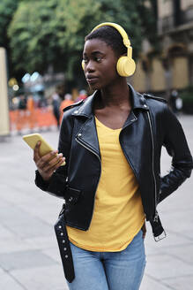 Young woman with headphones and mobile phone looking away while walking on footpath - AGOF00027