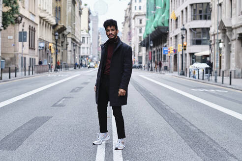 Young fashionable man staring while standing on road in city - AGOF00030