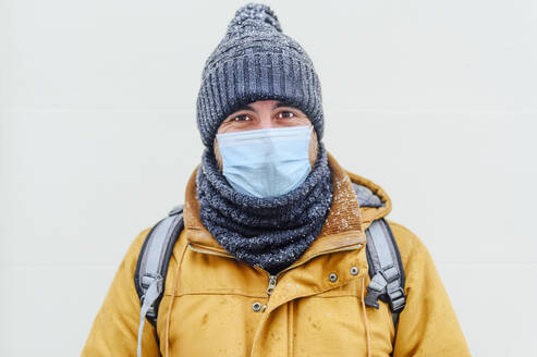 Man in warm clothing against white wall during pandemic - PGF00412