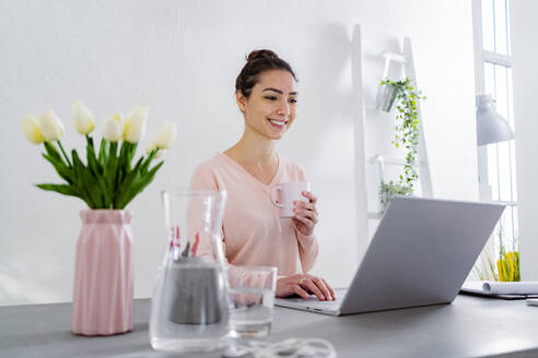 Smiling woman drinking coffee while working on laptop at home - GIOF11032