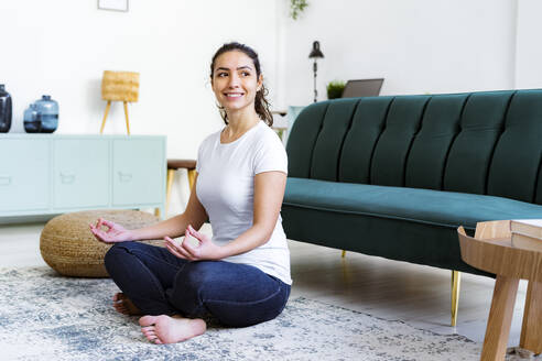 Young woman smiling while doing yoga sitting at home - GIOF11053