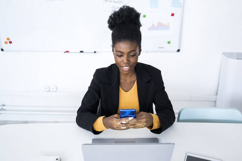 Young female entrepreneur text messaging through smart phone while sitting with laptop at desk - GIOF11121