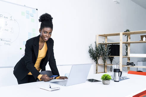 Smiling young Afro female entrepreneur using smart phone while leaning by laptop at desk - GIOF11124