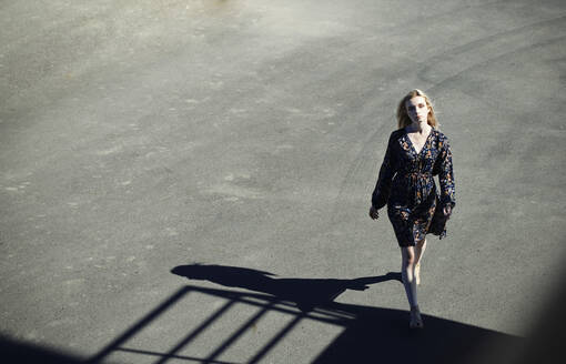 Young woman walking on road during sunny day - AZF00153