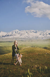 Young woman sitting on chair against cloudy sky - AZF00168
