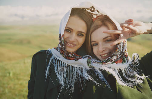 Beautiful woman showing peace sign with female friend on meadow - AZF00174