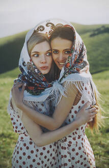 Surprised woman with female friend sharing headscarf while standing at meadow - AZF00177