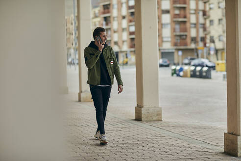 Man in casual clothing talking on mobile phone while walking in arcade - ACPF01117