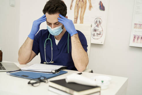 Worried male doctor with protective face mask sitting at desk while looking at documents - ABIF01335