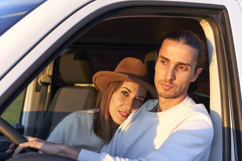 Woman embracing boyfriend while sitting in car - VEGF03873