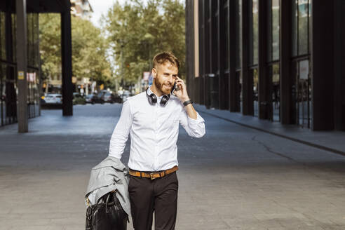 Businessman talking on mobile phone while walking on footpath - BOYF01780
