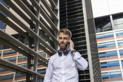 Mid adult businessman with headphones talking on mobile phone while standing in city - BOYF01786
