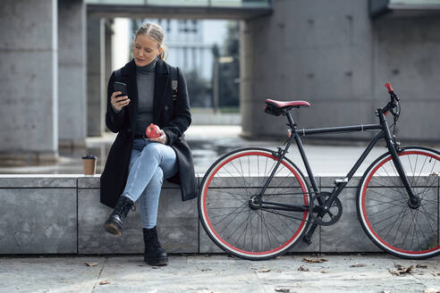 Young woman using mobile phone while sitting on retaining wall by bicycle - JSRF01400