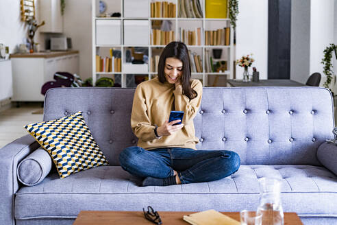 Young smiling woman using mobile phone while sitting on sofa at home - GIOF11180