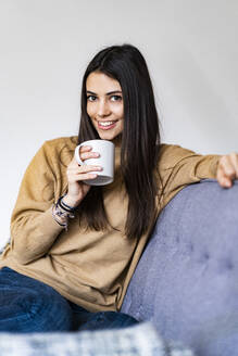 Woman drinking coffee while sitting on sofa at home - GIOF11189