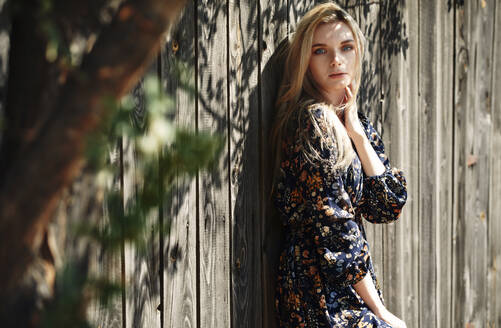 Beautiful woman with blue eyes leaning on wooden wall - AZF00185