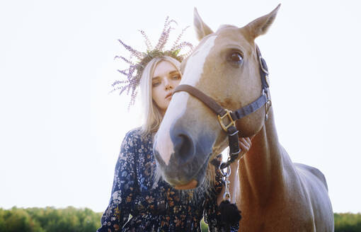 Woman wearing flowers holding horse against clear sky - AZF00191