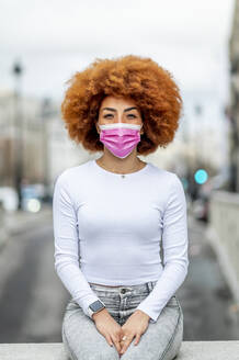 Mid adult woman wearing protective face mask while sitting on retaining wall - OCMF02065