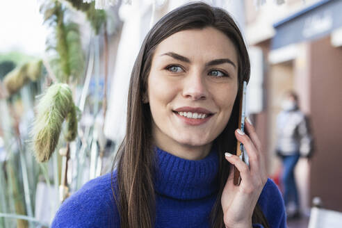 Smiling beautiful woman talking on mobile phone while looking away - PNAF00640