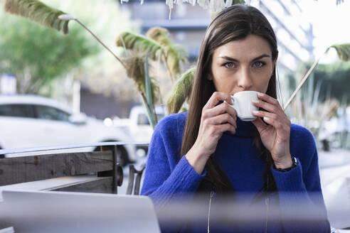 Woman with gray eyes drinking coffee in sidewalk cafe - PNAF00643