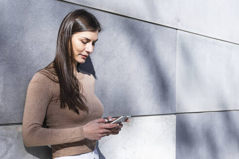 Smiling female entrepreneur using smart phone while leaning on wall - PNAF00646