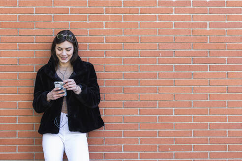 Smiling woman with mobile phone listening music while standing against brick wall - PNAF00649
