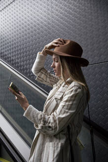 Woman with looking at mobile phone while standing on escalator - VEGF03907