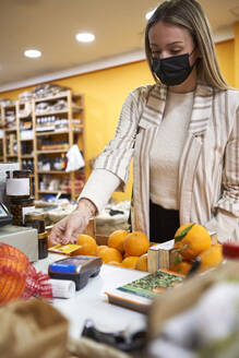 Young woman with protective face mask paying through credit card at store - VEGF03931