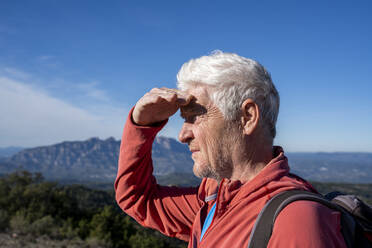 Senior man admiring view while standing against sky at Sant Llorenc del Munt i l'Obac, Catalonia, Spain - AFVF08156
